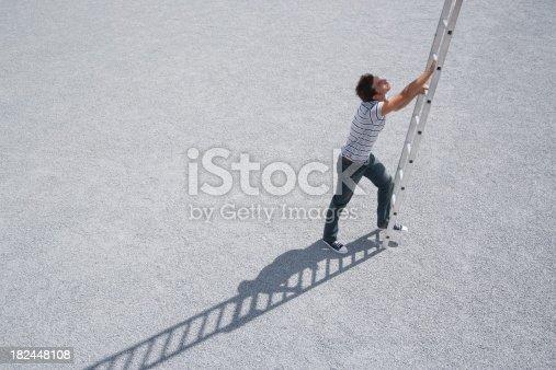 istock Man climbing ladder outdoors 182448108