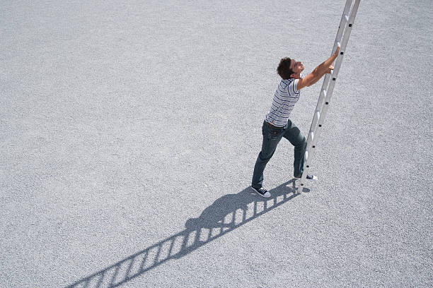 Homem subindo a escada ao ar livre - foto de acervo