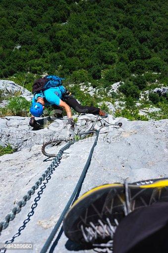 istock Man climbing on a rocky wall 694389660