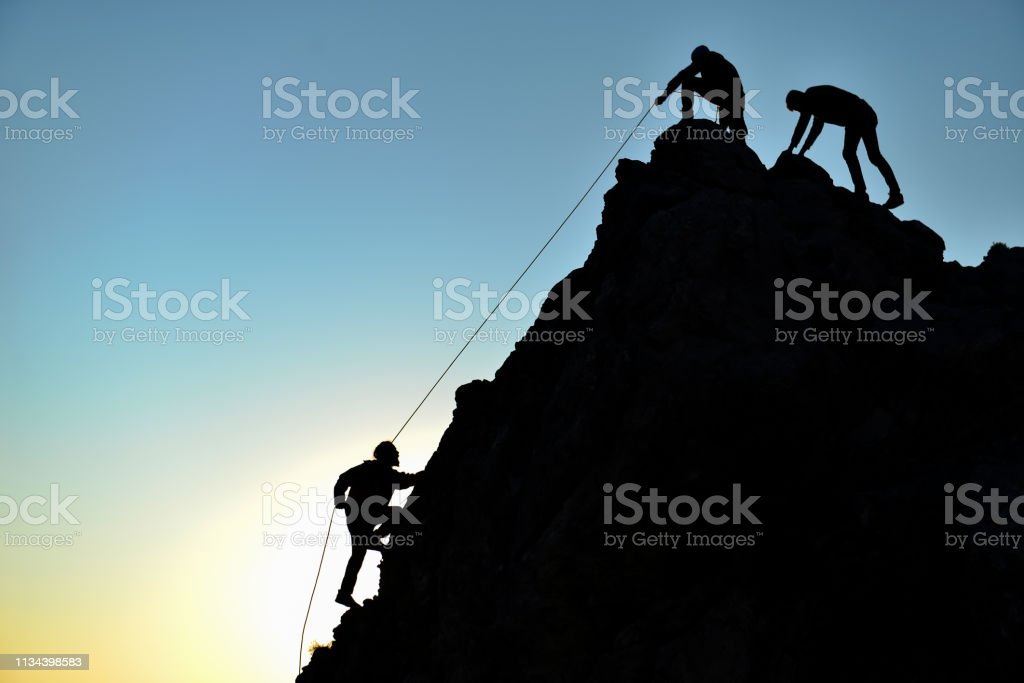 man climbing on rock with rope support stock photo