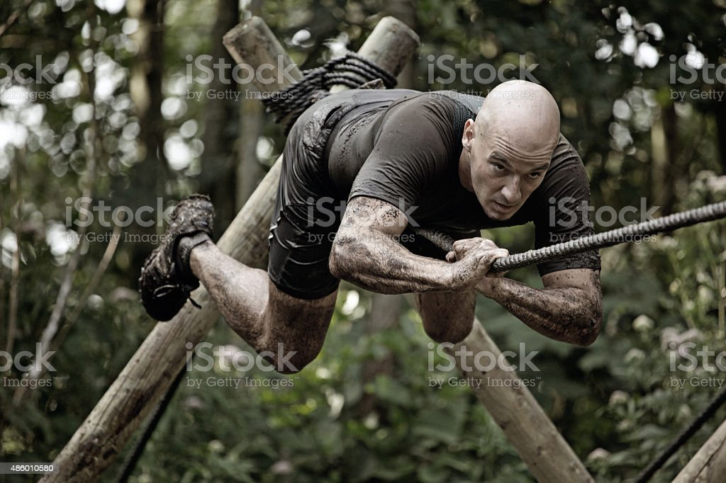 man climbing rope over mud obstacle stock photo