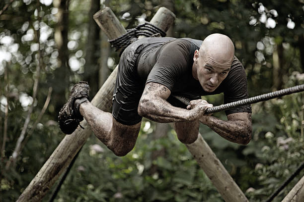 man climbing rope over mud obstacle man climbing rope over mud obstacle mud run stock pictures, royalty-free photos & images