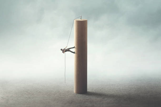 man climbing the tower with a rope stock photo