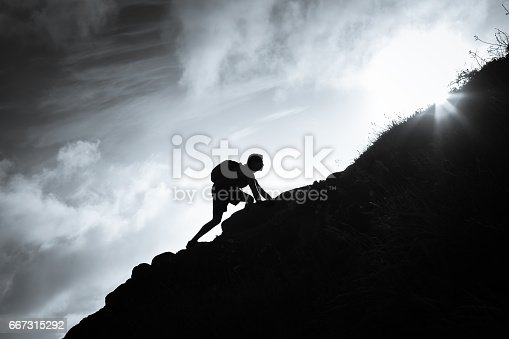 Black and white image of man climbing up a mountain.