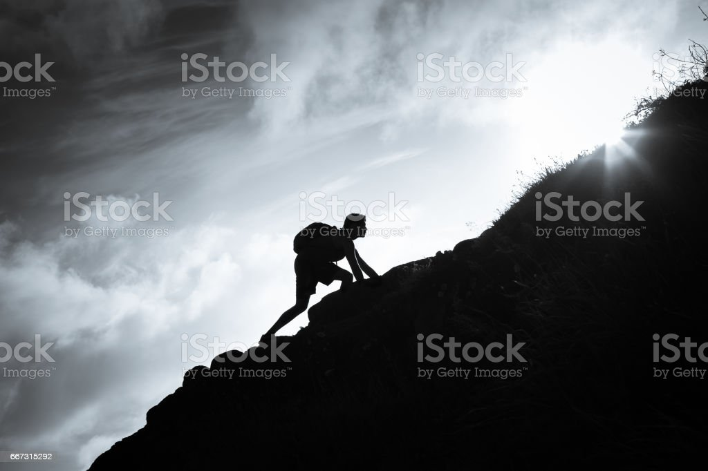 Man climbing up a mountain. stock photo
