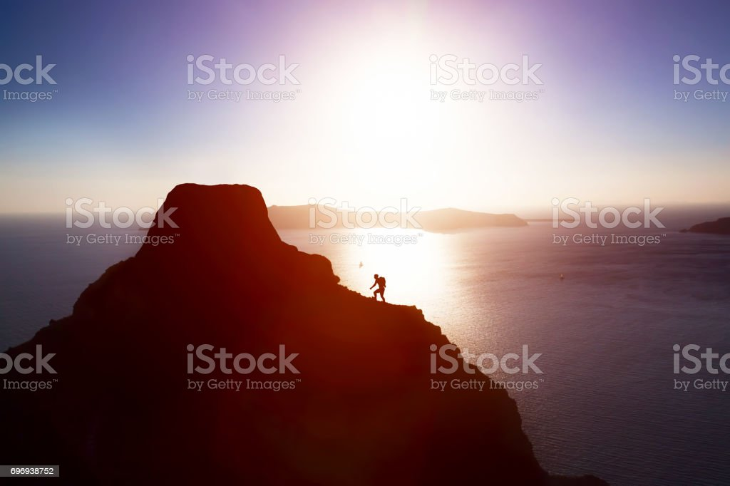Man climbing up hill to reach the peak of the mountain over ocean. stock photo