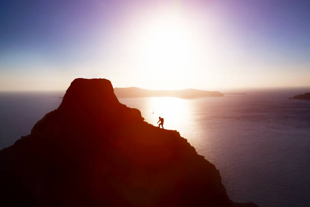 Man climbing up hill to reach the peak of the mountain over ocean. Man climbing up hill to reach the peak of the mountain over ocean. Persistence, determination, strength, reaching the target concepts. persistence stock pictures, royalty-free photos & images