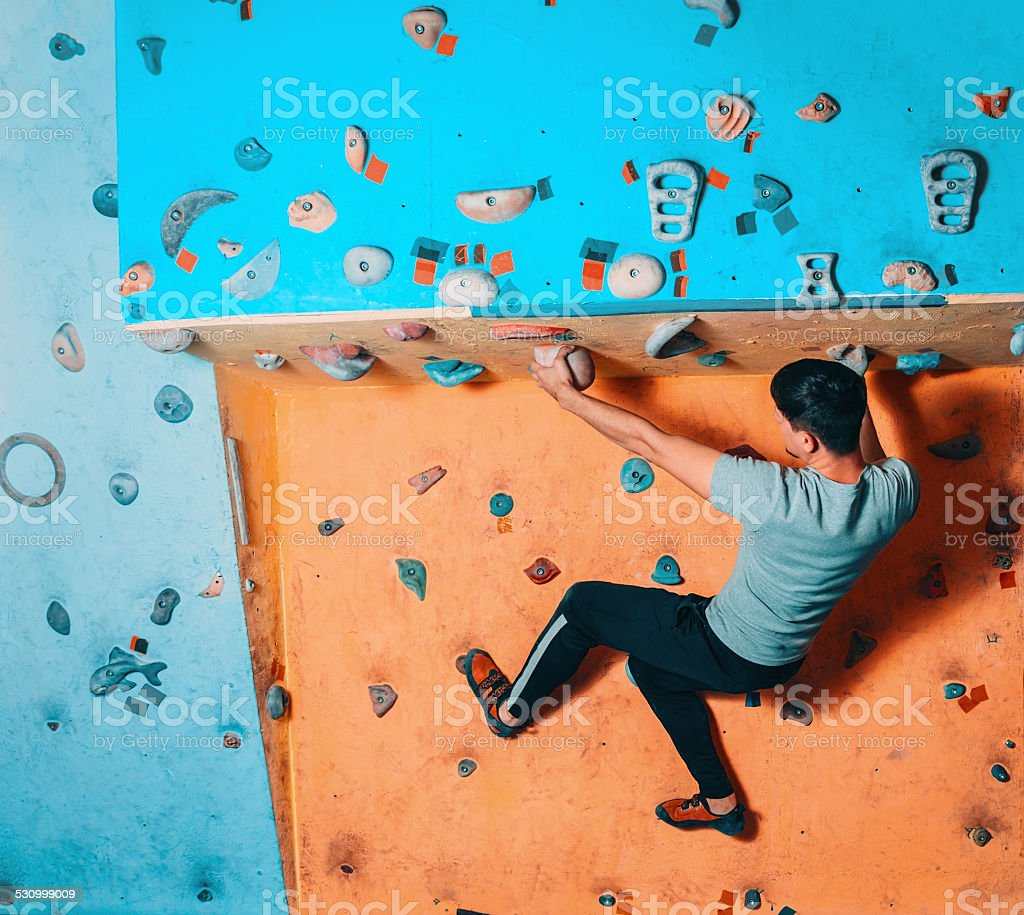 Man climbing up on practice wall stock photo