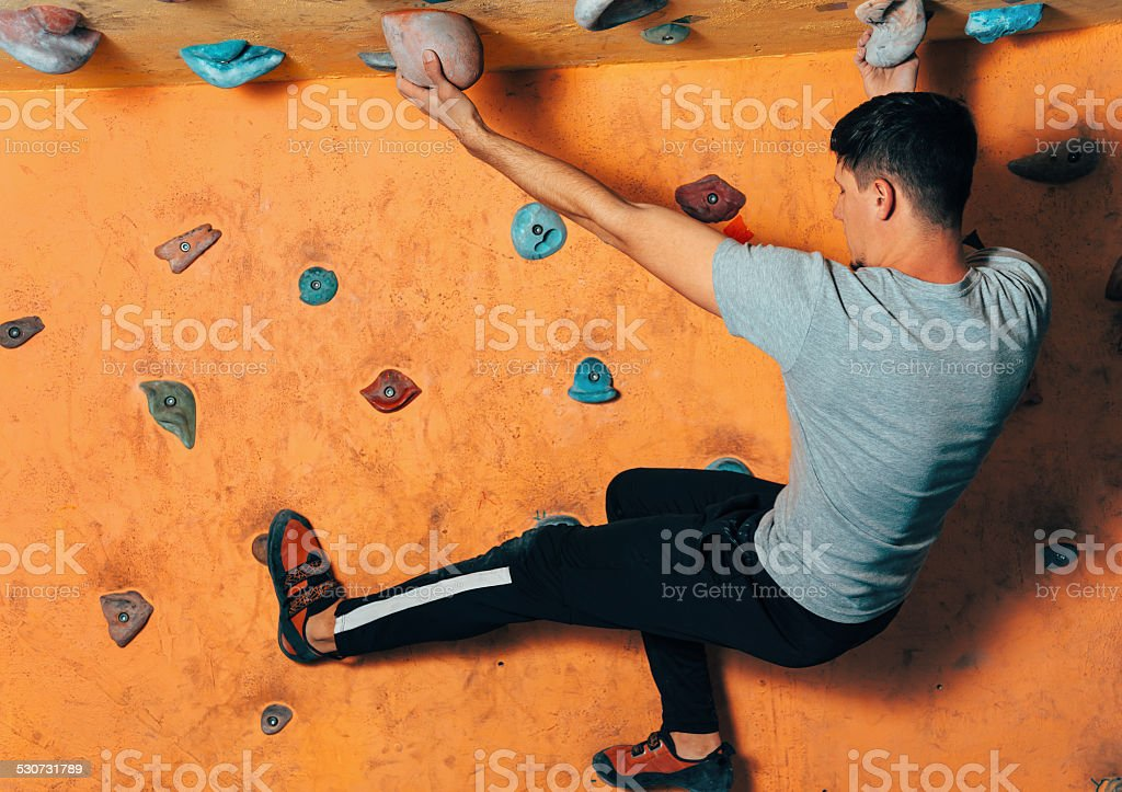 Man climbing up on wall indoors stock photo