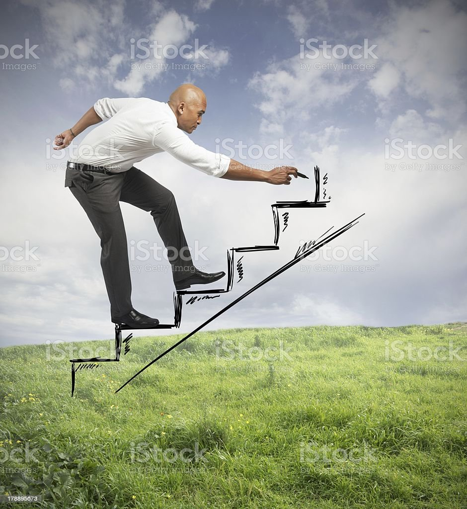 Man climbs drawn stairs and draws higher steps stock photo
