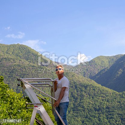 603993820 istock photo Man climbs ladder above forest 1210662141