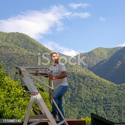 603993820 istock photo Man climbs ladder above forest 1210662142
