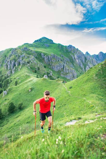 Mann erklimmt steilen Bergweg mit Stöcken – Foto
