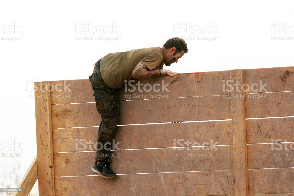 man climbs wall obstacle at a mud run obstacle course event stock photo