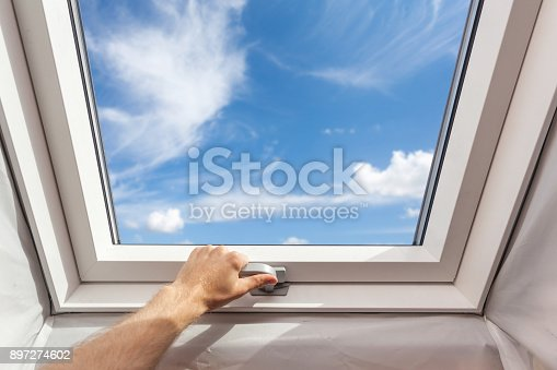 966792200 istock photo Man close new skylight (mansard window) in an attic room against blue sky 897274602