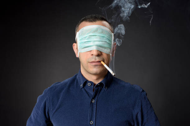 Man Closed His Eyes With A Protective Mask To The Potential Consequences Of Consuming Tobacco Products, And Still Smoking A Cigarette, COVID-19 Concept stock photo