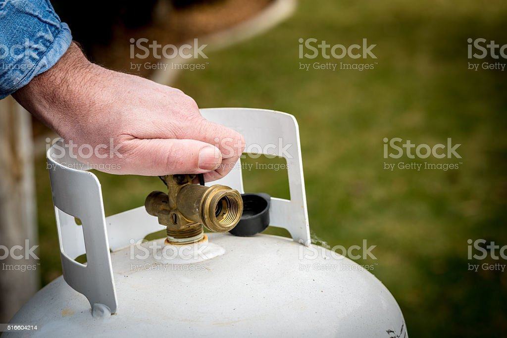 Man closes a knob on a propane tank stock photo