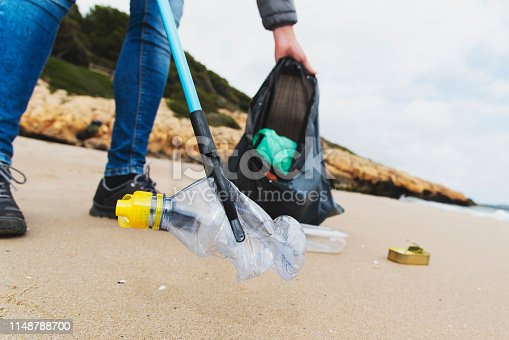 istock man collecting garbage on the beach 1148788700