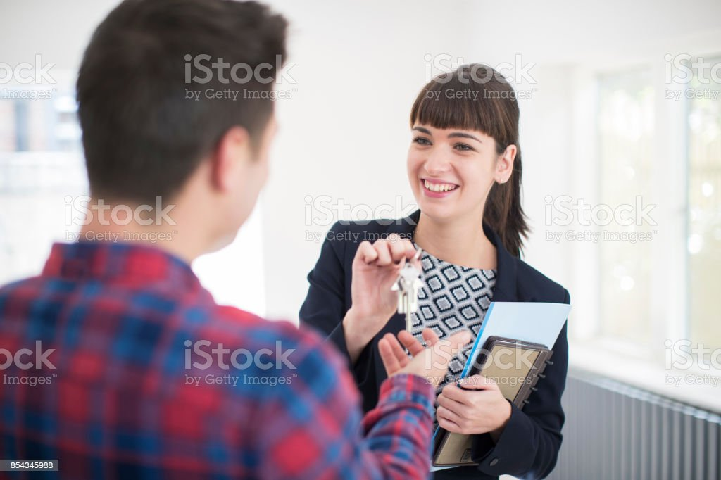 Man Collecting Keys To New Home From Female Realtor - Royalty-free 20-29 Years Stock Photo