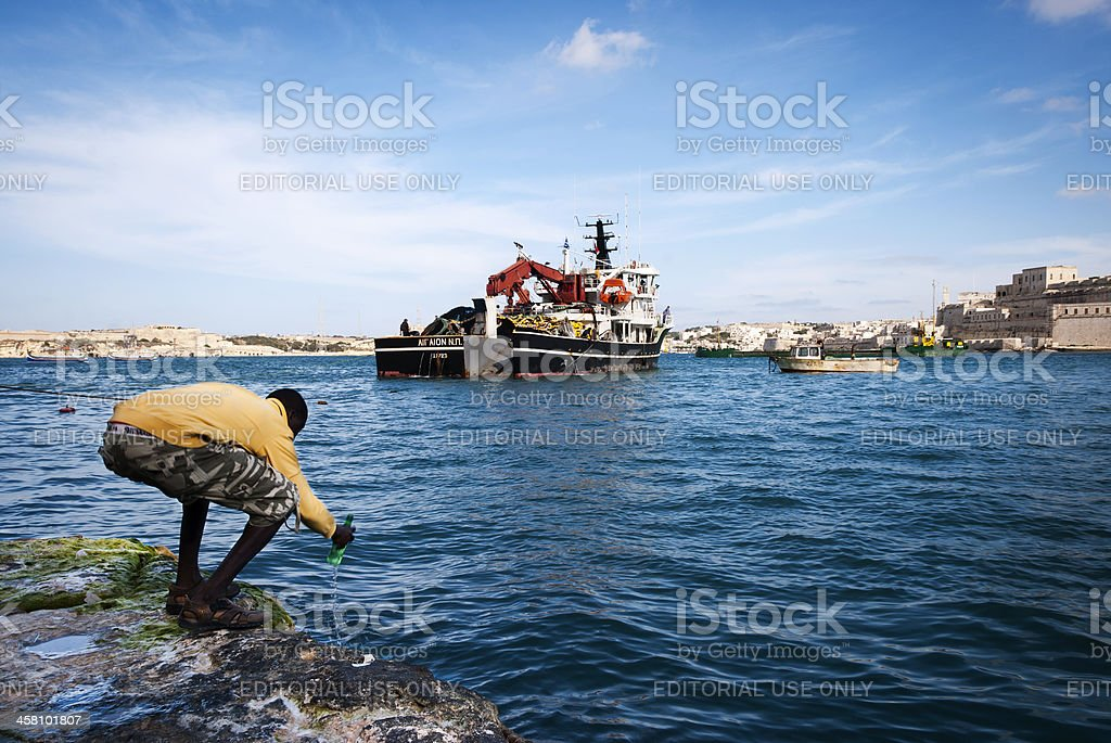 Man collecting sea water in the Grand Harbour, Valletta, Malta royalty-free stock photo
