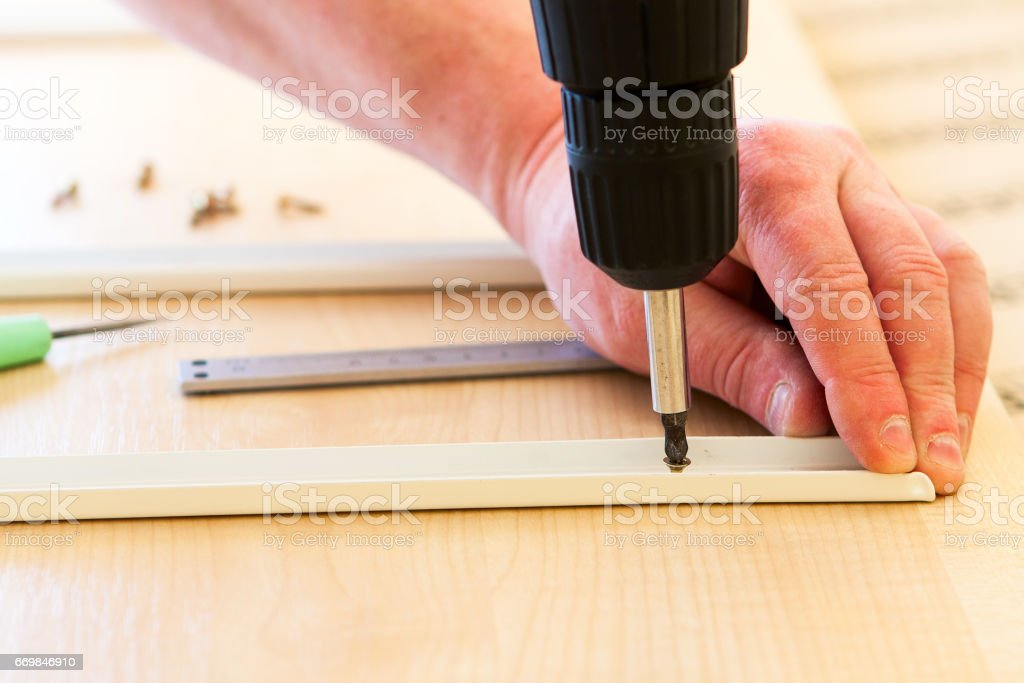 man collects furniture fittings stock photo