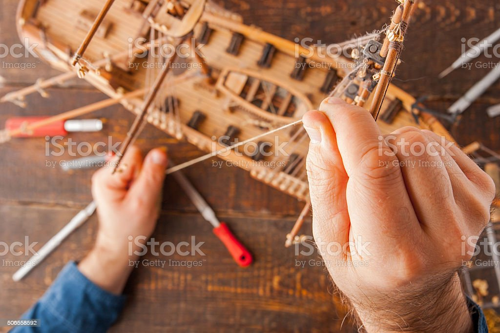 Man collects the vehicle model on the wooden table stock photo