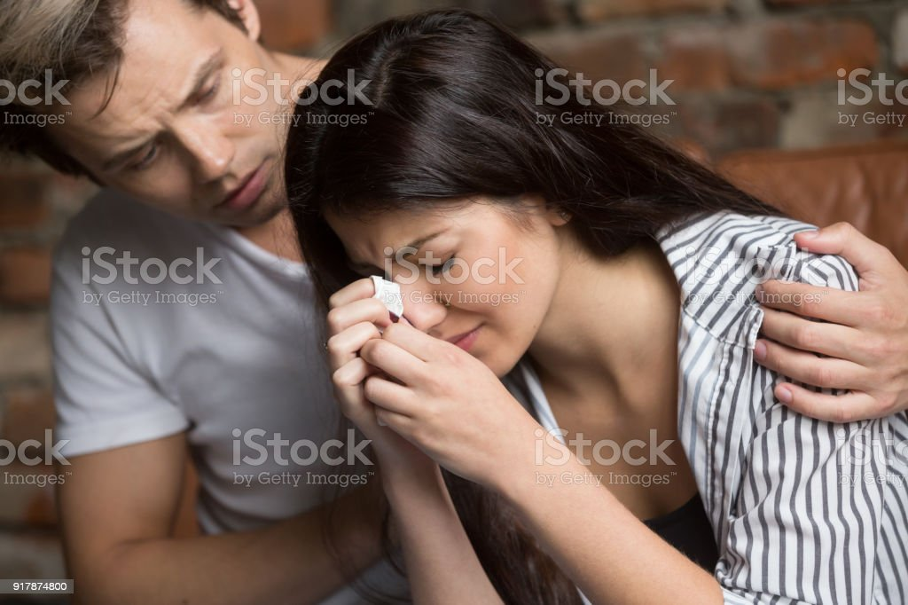 Man comforting crying sad woman, friend consoling girl in tears stock photo