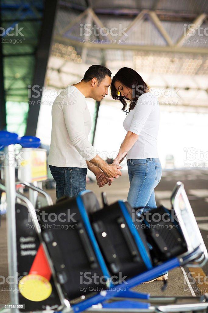 man comforting his girlfriend at airport stock photo