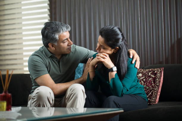 Man comforting his wife at home stock photo