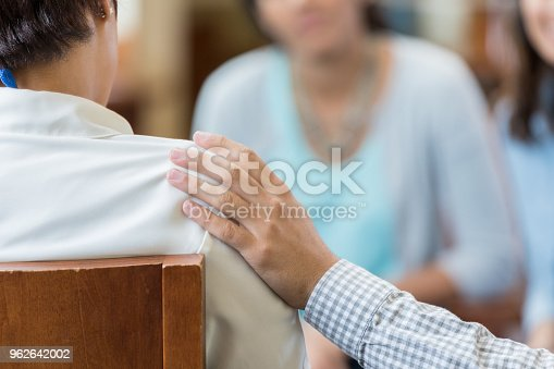 Unrecognizable man comforts woman during a support group or group therapy meeting. His hand is on her shoulder.