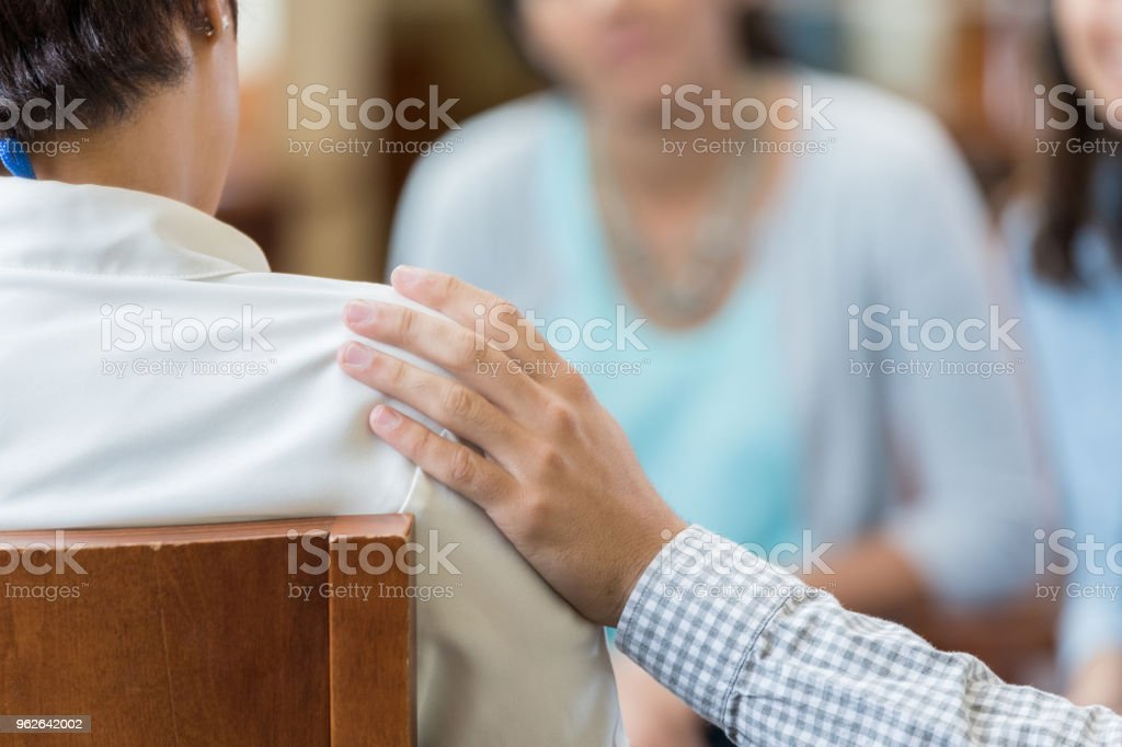 Man comforts woman during counseling session stock photo
