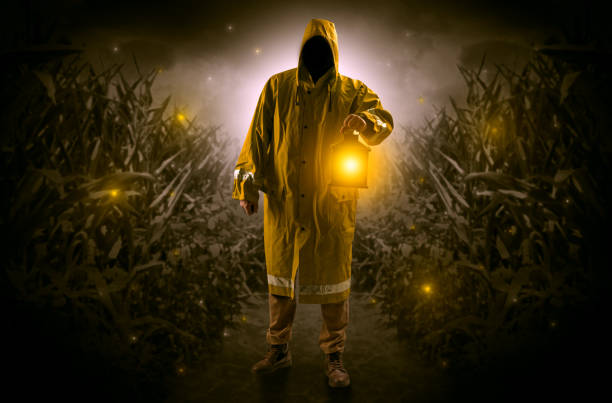 Man coming out from a thicket with lantern Man in raincoat at night coming from thicket and looking something with glowing lantern bootes stock pictures, royalty-free photos & images