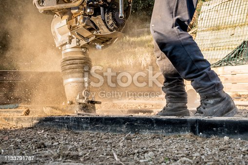 Man Compacting Soil with Vibratory Rammer Tamper on Home Construction Site