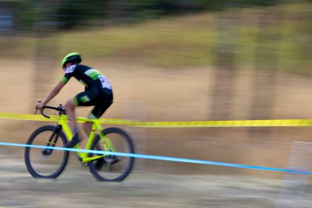 ein mann tritt in einem querfeldein-radrennen. - cyclocross stock-fotos und bilder