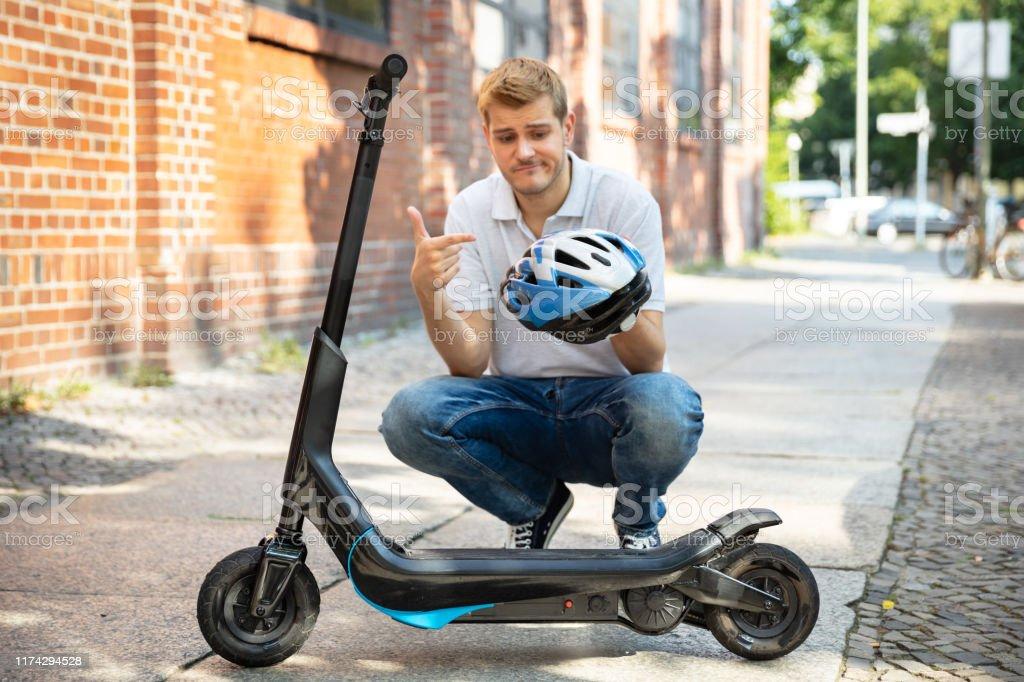 Hombre quejándose del casco para E-Scooter - Foto de stock de Adulto libre de derechos