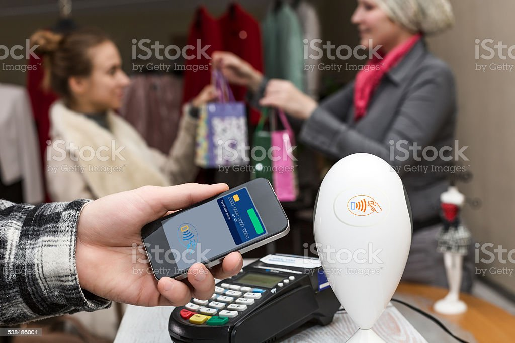 Man completing mobile Payment at Store Cashiers Desk with Terminal stock photo