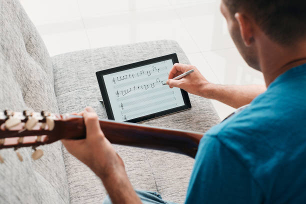 Man Composing Acoustic Guitar Sheet Music On Digital Tablet stock photo