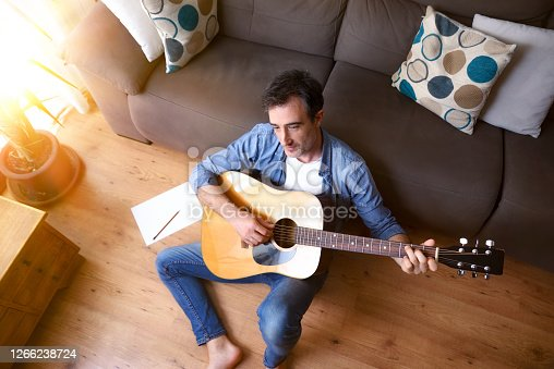 Man composing for guitar sitting on the floor in the living room at home. Top view.