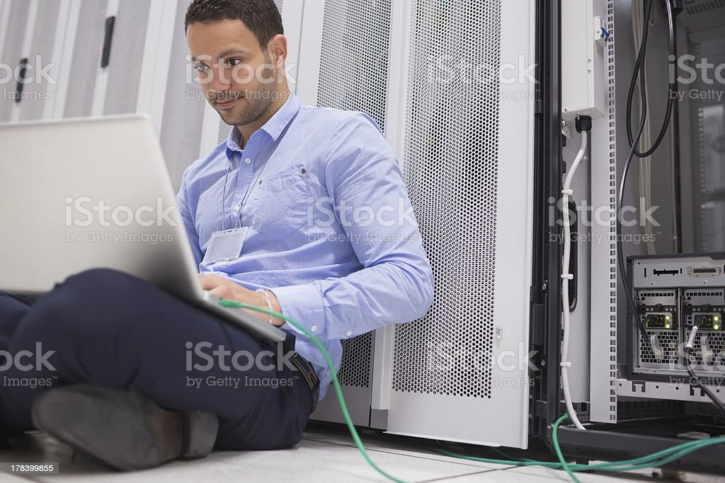 Man concentrating on laptop connected to server royalty-free stock photo