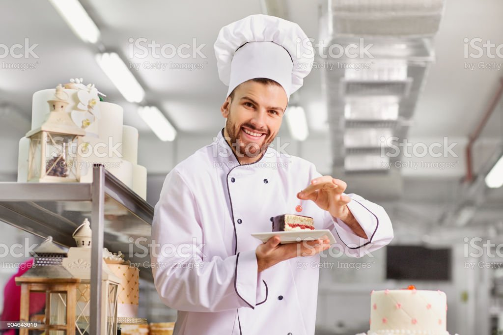 Man confectioner  with a cake in his hands in the pastr stock photo