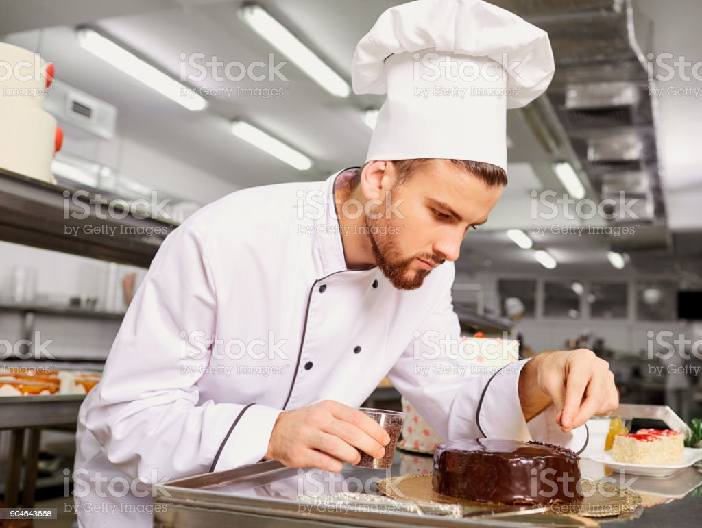 Man confectioner with a cake in his hands in the pastry stock photo