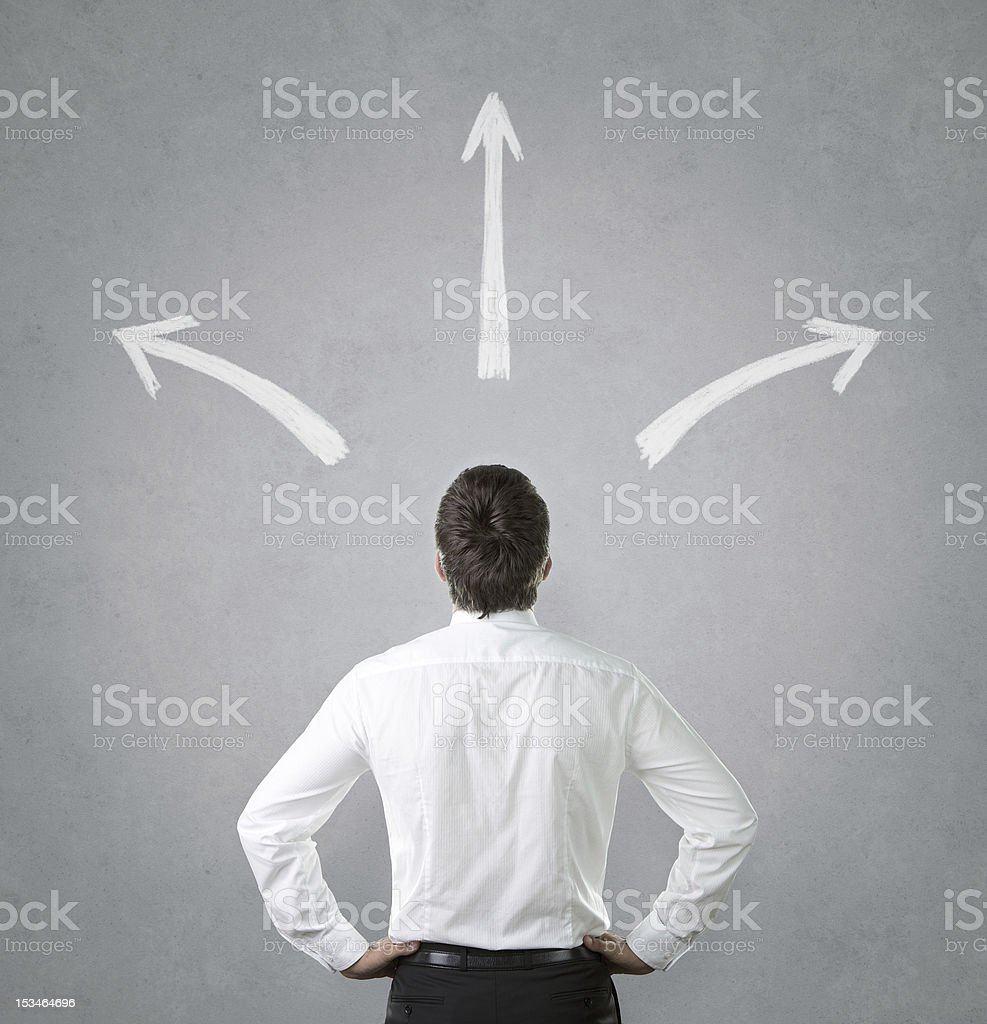Man confused by white arrows pointing everywhere stock photo