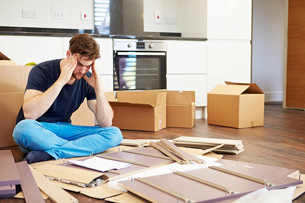 A man confused in putting together a self assembly furniture stock photo