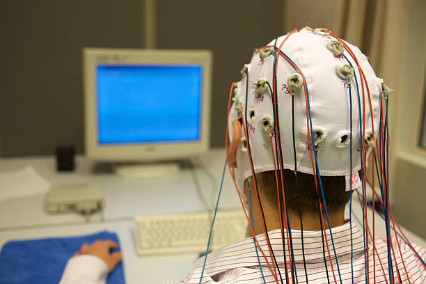 man connected with cables for EEG in front of monitor stock photo