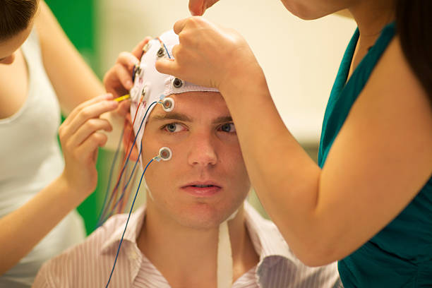 man connected with cables to computer - EEG for resarch stock photo
