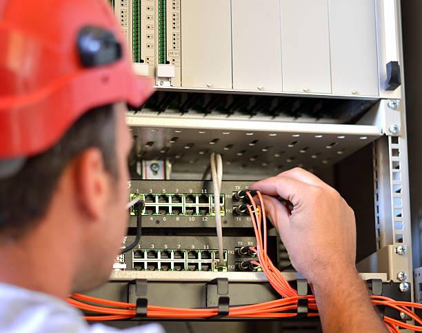 man connecting fiber optic cable to the switch - glasfaser telekommunikationsgerät stock-fotos und bilder