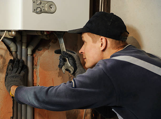 Man connects the gas boiler Man connects the gas boiler to the pipes with a wrench pipefitter stock pictures, royalty-free photos & images