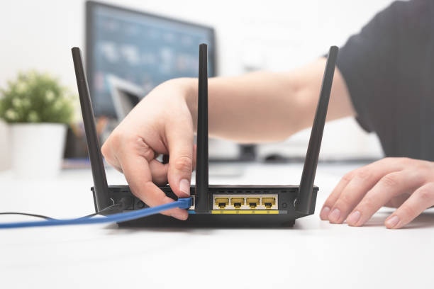 Man connects the internet cable to the router stock photo