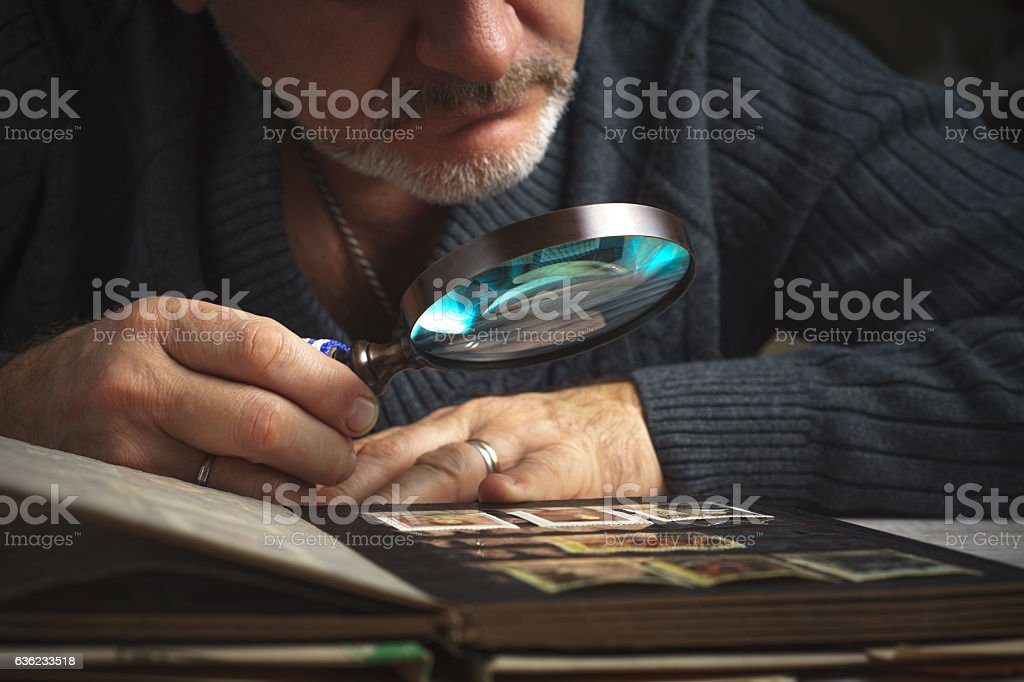 Man considers album of postage stamps trough magnifying glass horizontal stock photo