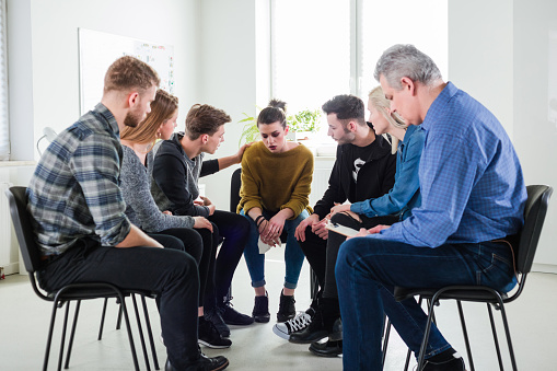 Man Consoling Depressed Friend In Group Therapy Stock Photo - Download Image Now